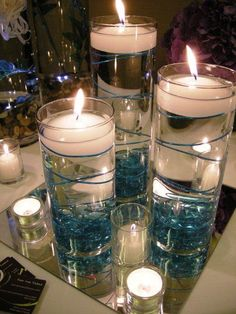I love the idea of cylinders with floating candle. Maybe finding a drinking glass set, put it on registry, use at reception, use in home after. What a great way to save money, re-purpose and keep a memory alive every day.  The mirror tiles can also be placed around the home, maybe with a picture frame collage, the ceiling around a light/chandelier #whatpainttouseonglassjars #floatingcandles