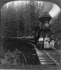 1906, Catching a ride on the Logging train...A logging train loaded with huge logs crossing a trestle in the Cascade Mountains, Ore.