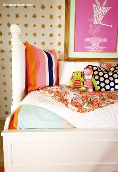 Kids room with bright bedding and a polka dot covered wall.