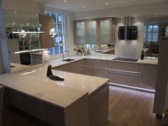 Beautiful, warm and inviting. This stunning kitchen installation consists of high gloss cashmere and white Silestone worktops. The mirror splash backs add the finishing touch to a striking room. #German #Kitchens #Mirror #Cashmere #HighGloss #Silestone #Falmec #Neff