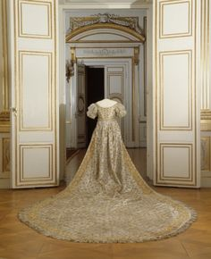 Coronation Dress of Queen Desideria, formerly Desiree Clary of silver silk embroidered with gold sequins forming crowns,belted empire waist, underdress of silver tulle lined with white tafetta also decorated with crowns. Bertha neckline with ten horizontal draped folds, train and gown has point d'Espagne bobbin lace in gold, originally on Lovisa Ulrika's coronation dress in 1751