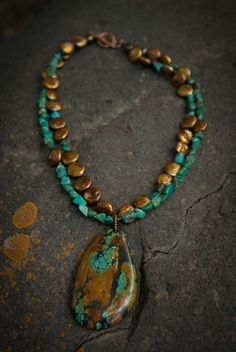 Gold coin pearls combine with deep green turquoise and a heavy matrix turquoise pendant in this custom necklace hand made in Colorado.