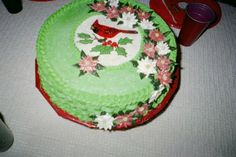 Christmas Cardinal cake. 10-in round, frosted in basket weave technique in buttercream.  Image drawn in icing gels with buttercream poinsettias.