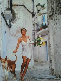 slinky white slip on dress flowers bouquet dog on a leash streets dark brown hair bun