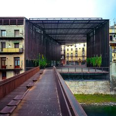 La Lira Theater Public Open Space, 2011, Ripoll, Girona, Spain In collaboration with Joan Puigcorbé  To form a covered public space for theatre productions, the architects built a slatted-steel box, with angled sides and open ends, over a plaza sandwiched between two old structures.  The volume faces a river and is connected to the opposite bank via a bridge made from the same material.