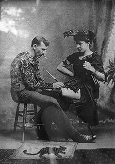 Gus Wagner hand poking a tattoo onto the thigh of his wife Maud Wagner in the 1900's 1897 : s'engage dans Marine marchande, revient et déclare que les indigènes de Bornéo lui ont enseigné l'art du tatouage. Tatoue entièrement Maud Stevens