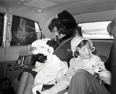 Jacqueline Kennedy, her hair and hat askew from the wind, holds her 2-month-old son, John F., Jr., while her daughter, Caroline, sits at her side, Feb. 4, 1961 in a limousine at Washington National Airport. The children flew to the capital from Palm Beach, Fla., to join their parents in the White House for the first time. (AP Photo)