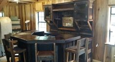 Barn wood bar that we built and set up in a cabin near Hokes Bluff, Alabama. The bar has 4 stools and sits in front of a large bar cabinet. We used an old rake for a wine glass holder and put glass in the doors on top to display items. This will look even better once it's decorated and has some people sitting around it....