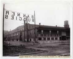 "Horizontal, black and white photograph showing the Banner Buggy Company on Rutger Street. The Iron Mountain railroad tracks can be seen in the foreground. A backward sign reading ""Banner Buggies"" hangs across the street on the left side of the image. A water tower in the background on the right side of the photograph also has a sign reading ""Banner Buggies"".  A typed note pasted to the bottom of the print reads: ""Banner Buggy Co., Rutgers st., & Iron Mt. tracks. Dr. Wm. G. Swekosky.""…"