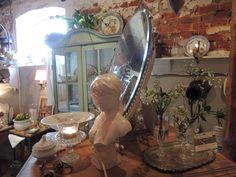 De dame tussen oude glaasjes met wat bloemetjes en oude Engelse spiegel, mooi sfeertje.