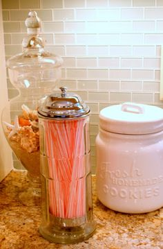 kitchen counter decor: a straw container and a fun apothecary jar w/ seasonal inspiration, i.e. shells for summer.