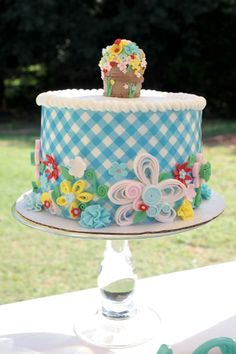Little House on The Prairie Party.The cake was a wonderful collaboration between baker and fondant artist!  The blue gingham reflected the fabric of the time, and the flowers were chosen to represent all of the prairie flowers.  A simple wooden barrel of flowers was the perfect topper~