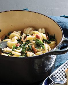 This pasta softens the bitterness of broccoli rabe with salty bacon and crunchy-sweet walnuts for a quick supper.
