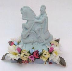 Imagens de santo coloridos em gesso com pedestal e flores.