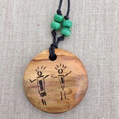 This natural wood hickory pendant, turned on a lathe, features two woodburned petroglyph shapes celebrating friendship. The wood burning adds to
