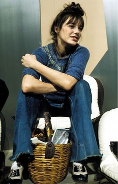 Jane Birkin wears a blue knit sweater with raw hem flare jeans and oxfords