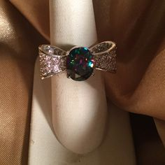 Mystic Topaz Ribbon Ring Ribbon rings are timeless,  this one here looks romantic. Sterling silver setting,  ribbon is set with white topaz.  Lots of sparkle here.  Everyone will ask,  Where did you get that ? Nwot Jewelry Rings