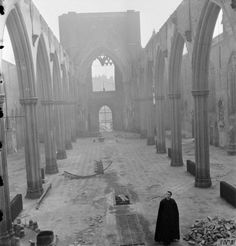 Father Dixon stands in the roofless shell of St George's Roman Catholic Cathedral, on the corner of St George's Road and Lambeth Road in Southwark, South East London. The Cathedral was severely damaged by an incendiary bomb attack which gutted the building on 16th April 1941.