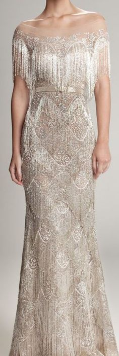 light beighe beaded, evening gown with fringe trim and off the shoulder.
