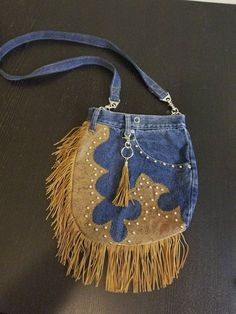 A unique custom made, western style fringed denim purse that coverts from a no hands waist/hip pouch to a cross body bag or shoulder purse. Roomy front pocket and secure back pocket help you keep organized. Made from re-purposed blue jeans, its the perfect bag for any occasion. Take it dancing, wear