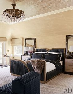 Brass is prevalent in the master bedroom, from the space-age Italian light fixture to the custom-made bed; the ebonized and inlaid mirrors are vintage Italian, and the fur throw is by Adrienne Landau.