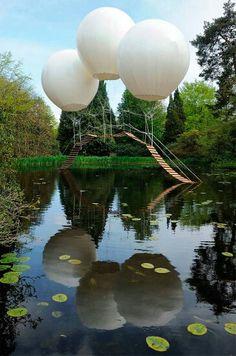 """Puente de globos, Reino Unido  El artista francés Olivier Grossetete creó una sublime instalación denominada """"Pont de Singe"""". Consta de un ligero puente suspendido por tres globos de helio dispuesto sobre un lago del Tatton Park en el Reino Unido. La instalación onírica del artista francés evoca una delicadez y fantasía abstracta. Formó parte de la bienal 2012 del Tatton Park."""