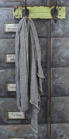 This fine knit scarf from becksondergaard in supersoft cotton has a very narrow black and white stripe running horizontally, and tapered ends.