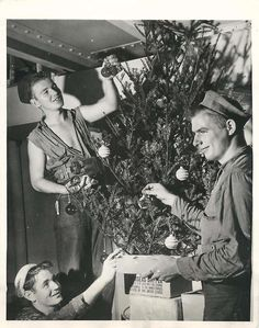 young coast guard veterans hang decorations on a christmas tree aboard a cargo ship moving through