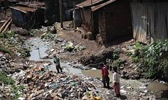 Three young residents of the second largest slum in African, Kibera, walk on…