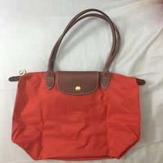 Longchamp Tote AUTHENTIC. Bought while in Paris. A cute burnt orange color (called 'poppy'). Very faintly dirty on bottom corners, otherwise in perfect condition. Measures 14.75 in. long, 9.5 in. in height & handles (from zipper to top) is about 8 in. Longchamp Bags Totes