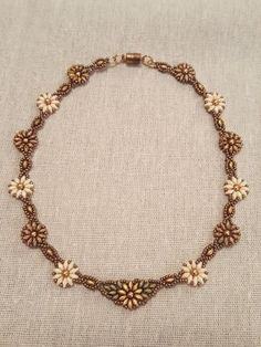 This beautiful handmade necklace features white, gold, and light brown flowers in a circular vine that drapes perfectly around the neck. Made from