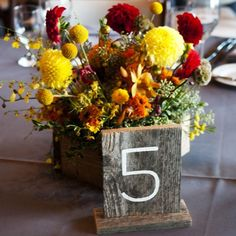Wooden Table Numbers Lively red, orange, and yellow flowers complement a rustic table number sign. Photo Credit: Two One Photography