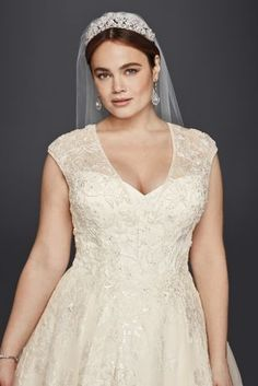 """When we say """"wow factor,"""" this plus size ball gown is what we mean. The opulent layers of tulle and lace appliques give the skirt fabulous texture, and the deep V-neckline and cap sleeves on the beaded bodice frame your face beautifully.  Oleg Cassini, exclusively at David's Bridal  Plus size  Polyester  Chapel train  Removable coverage panel at neckline  Pockets  Button-back closure; fully lined Dry clean"""