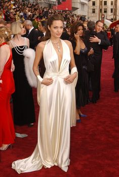 2004 - The Oscars - 76th Academy Awards -  Angelina Jolie was subdued yet sultry in a white satin gown by Marc Bouwer. The sexy halter-style dress featured a draped front and long back tie.