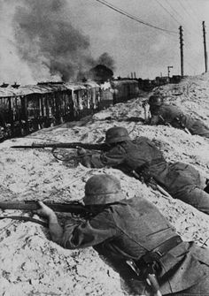 German soldiers shooting at russians from atop an embankment on the Eastern Front.