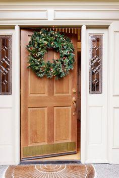 Najprostszą dekoracją świąteczną wejścia do domu jest wianek świąteczny. Oto tradycyjna wersja z świerkowymi gałązkami. Fot. Shutterstock.
