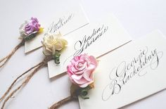 Floral wedding place name cards with pastel coloured roses
