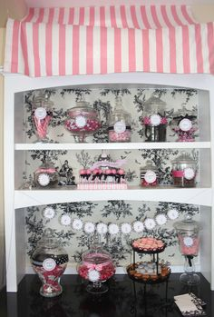 """French confections: """"I used toile fabric to line the back of the shelves, then used pink and white striped material as an awning. I threaded fishing line through wrapping paper tubes and thumbtacked the lines to the ceiling in order to create it.""""  {Cakes Like a Party}"""