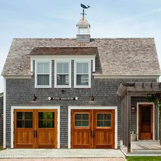 The striking wood finish on the garage doors adds warmth and charm to this home's exterior. More great garage doors: http://www.bhg.com/home-improvement/garage/ideas-inspiration/garage-door-styles/?socsrc=bhgpin062413woodgarage=12