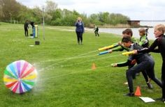 Build an outdoor racing course and have team try to get their balls through the course only using water guns.   Use cones or string to build your course
