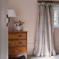 Susie Watson Designs - Susie Watson Designs Fabric Collection - A wood chest of drawers with a clear and white table lamp, a jug vase, and floor-length grey, pink and green floral curtains Soft Furnishings, Decor, Cottage Interiors, Home, Interior, Curtains Bedroom, Country Cottage Bedroom, Cottage Curtains, Home Decor
