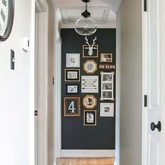 an accent wall at the end of the hallway acts as a backdrop for a gallery. Also note millwork's white paint that provides contrast.