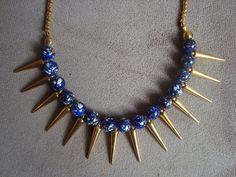 Colar confeccionado com spikes de metal dourado intercalados com contas de resina azul marinho rajadas de branco e dourado. Corrente em metal dourado. R$74,00