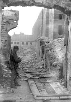 An SS soldier standing amongst the ruins in the Warsaw ghetto during the suppression of the uprising.
