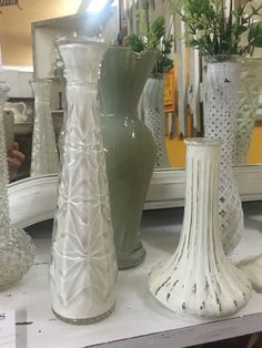 Inexpensive glass vases (which over flow the shelves in thrift stores ) painted with chalk paint creating a big makeover with a shabby chic flair.
