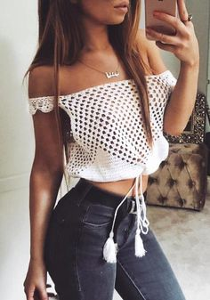 Model wears white crochet cutout off-shoulder crop top with black pants