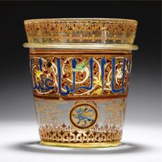 A HIGHLY IMPORTANT MAMLUK GILDED AND ENAMELLED GLASS BUCKET OR FINGER-BOWL, SYRIA OR EGYPT, MID-14TH CENTURY, made of thick glass with a brownish tinge and some large and many tiny bubbles, of slightly flaring cylindrical form with a raised flange to the exterior below the mouth, the sides decorated with a blue enamelled inscription set against a winding white scroll with animal terminals in green, yellow, white and black interspersed with red leaves,
