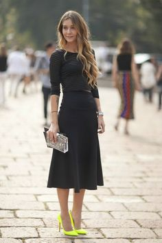 Semi-sheer black striped top is paired with black high-waisted midi skirt. The look is completed with bright yellow pumps and eye-catchy clutch: