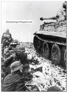 German soldiers under cover of a Tiger tank from the 502th battalion of heavy tanks at Narva, Estonia. February 1944.