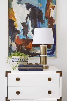 Instead of buying an expensive sofa, splurge on a painting you can hang above the couch that will elevate the room.